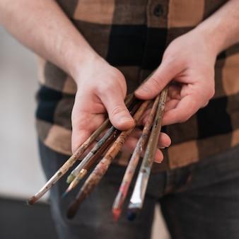 Primo piano delle spazzole di pittura della tenuta dell'uomo