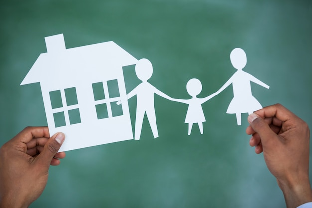 Man holding paper cut out family and house
