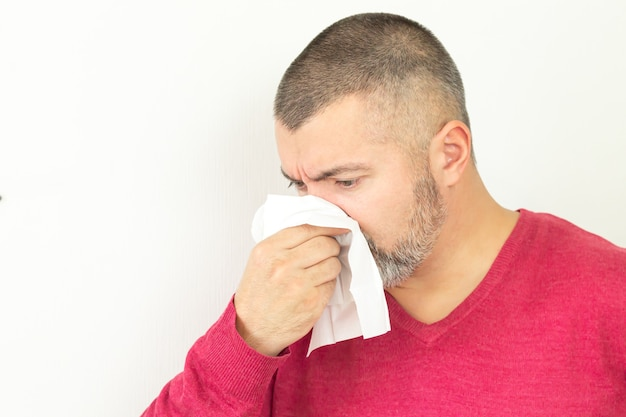 Man holding paper handkerchief and sneezing on white background