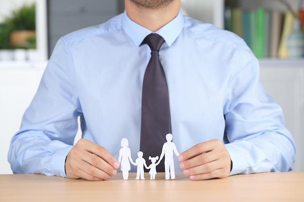 Человек, держащий бумажный силуэт семьи, сидя за столом. страховая концепция