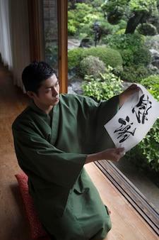 Uomo con in mano un foglio con grafia giapponese