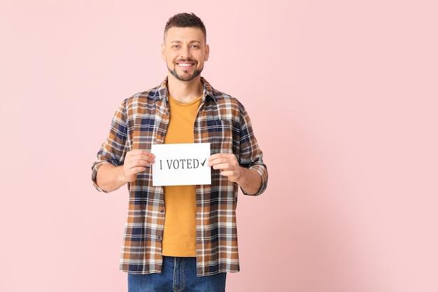 私が投票したテキストが書かれた紙を持っている男性