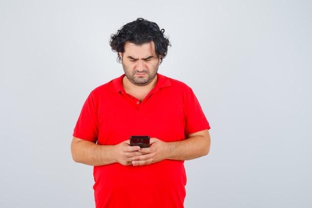 赤いtシャツを着て携帯電話を手に持って集中して見える男