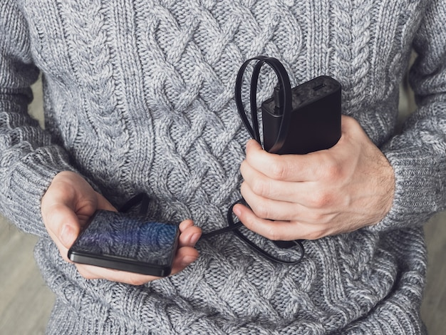 Man holding a phone and a power bank