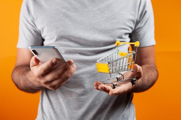 Man holding phone and shopping cart on orange background