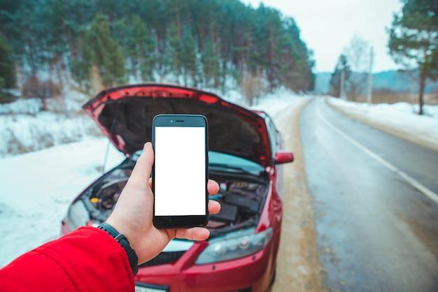 Человек, держащий телефон белый экран сломанный двигатель автомобиля на фоне. помощник в дороге