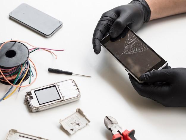 Мужчина держит телефон с разбитым дисплеем