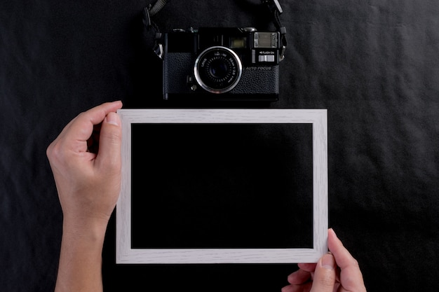 Man holding photo frame and a retro film camera on black background. world photography day.