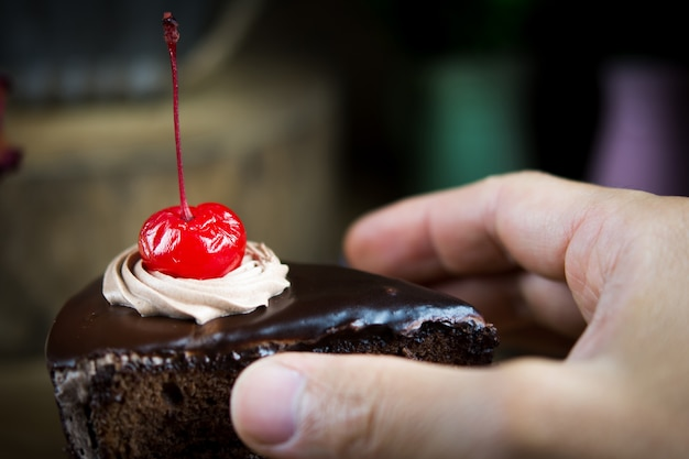 Man holding piece of delicious chocolate cake, closeup.