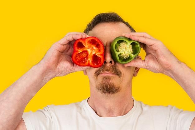 眼鏡のように彼の目に赤と黄色のピーマンの断片を保持している男