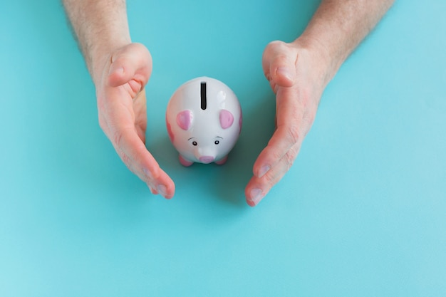 Man holding piggy bank on blue background