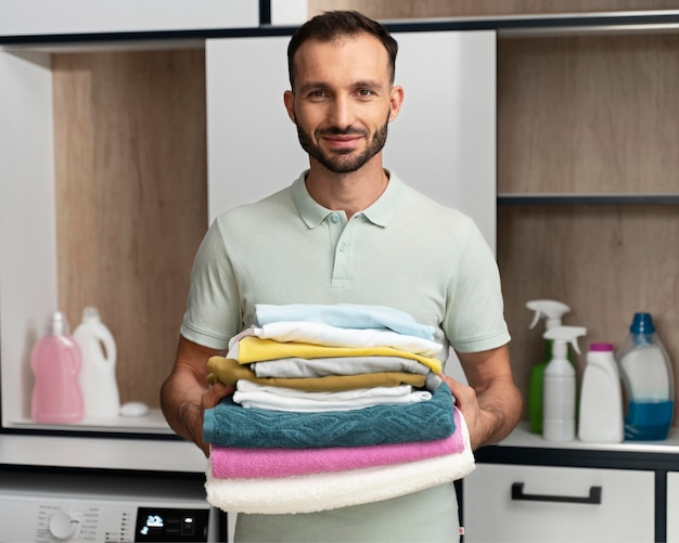Man holding a pile of clean clothes
