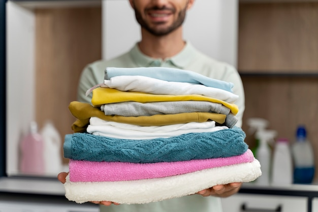 Uomo con una pila di vestiti puliti