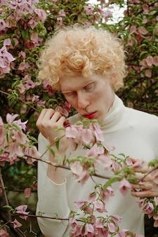 Uomo che tiene fiori rosa in posa nel parco
