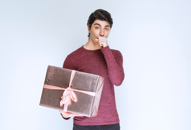 Man holding a pink gift box and caughing.