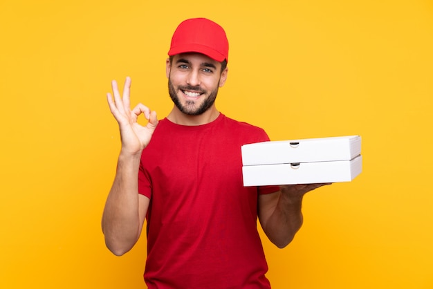 Man holding pizzas boxes over isolated wall