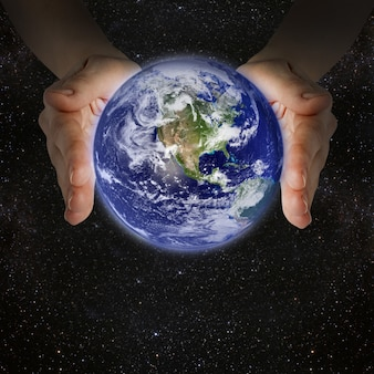 Man holding the planet earth in the hands against the wall of the galaxy.