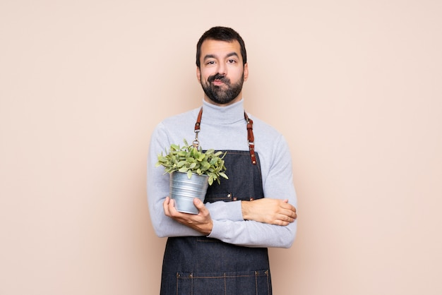 Man holding a plant over isolated background feeling upset