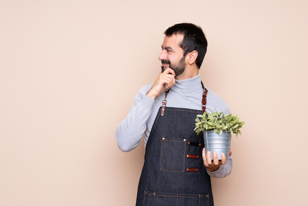 Man holding a plant over isolated background looking to the side