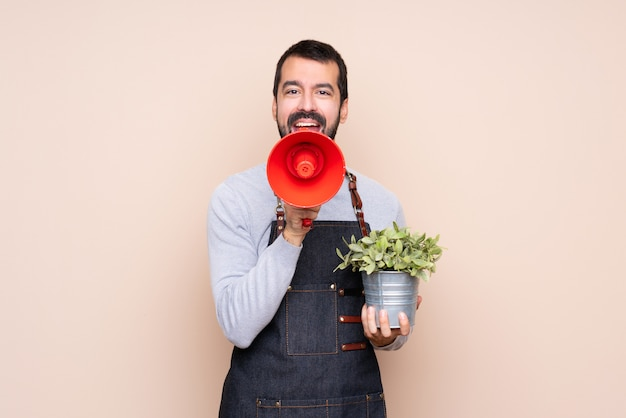 Man holding a plant over isolated background shouting through a megaphone