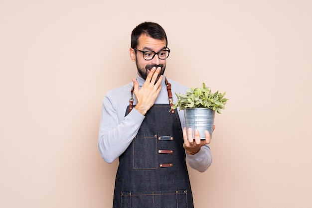 Man holding a plant over isolated  with glasses and surprised