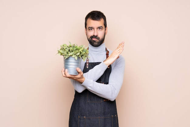 Man holding a plant making no gesture
