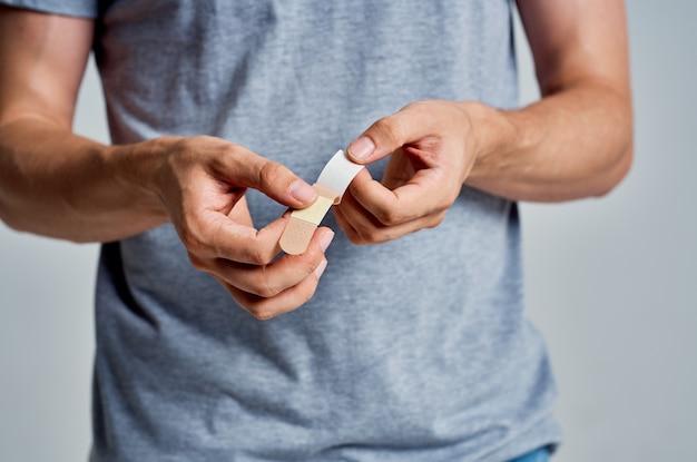 手の治療の助けで石膏を保持している男
