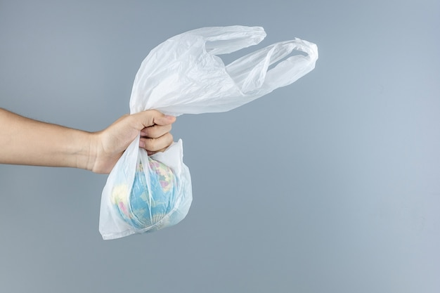 Man holding plastic bag and globe inside with copy space for text. environmental protection, zero waste, reusable, say no plastic, world environment day and earth day concept