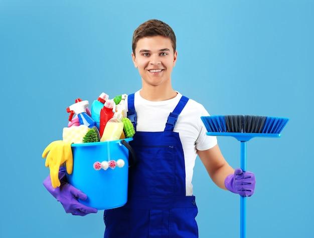 Мужчина держит пластиковое ведро с щетками и моющими средствами на сером