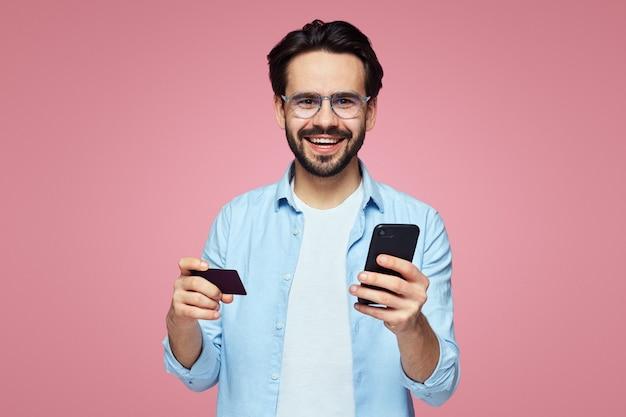 Человек, держащий пластиковую кредитную карту и мобильный телефон, изолированные на розовой стене