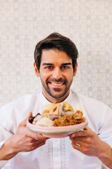Человек, держащий тарелку восхитительной арабской пищи