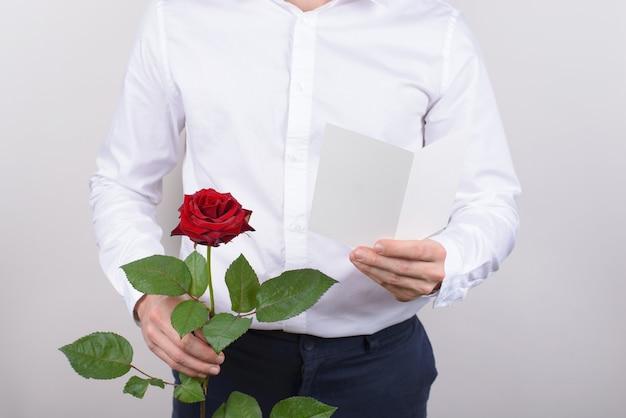 Мужчина держит открытку и розу изолировал серый фон