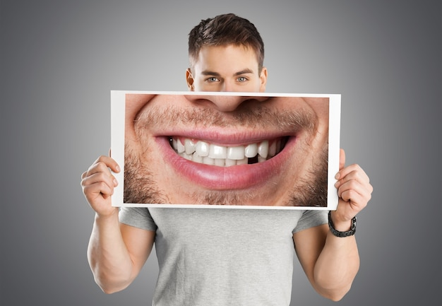 Man holding poster with smile on grey background