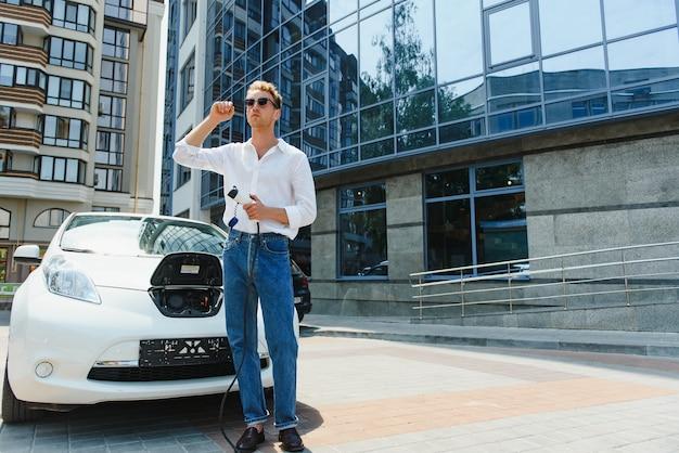 Человек, держащий зарядный кабель для электромобиля на открытой автостоянке. и он собирается подключить машину к зарядной станции на стоянке возле тц.