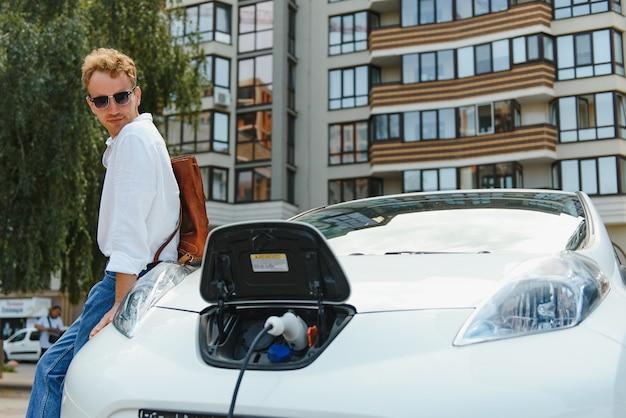 야외 주차장에서 전기 자동차에 대 한 전원 충전 케이블을 들고 남자. 그리고 그는 쇼핑 센터 근처 주차장에 있는 충전소에 차를 연결하려고 합니다.