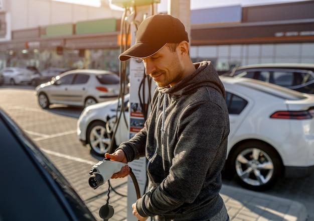 야외 주차장에서 전기 자동차에 대한 전원 충전 케이블을 들고 남자