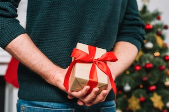 Man holding present behind back