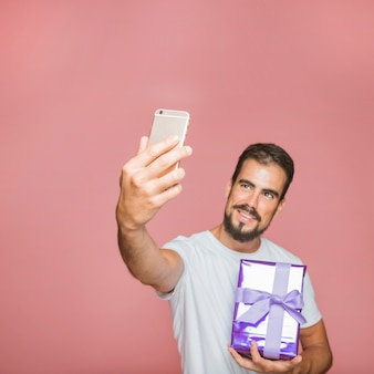 Man holding present taking selfie against pink background