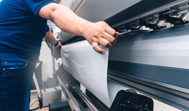 대형 인쇄 플로터에 인쇄 가능한 자료를 들고 있는 남자