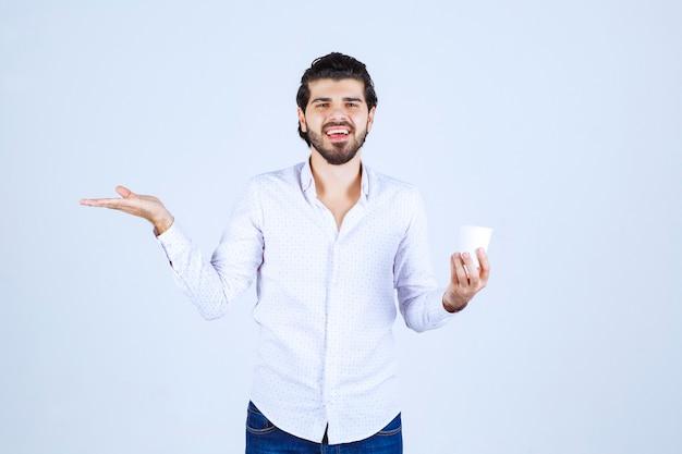 Uomo che tiene e promuove una tazza di caffè o un caffè