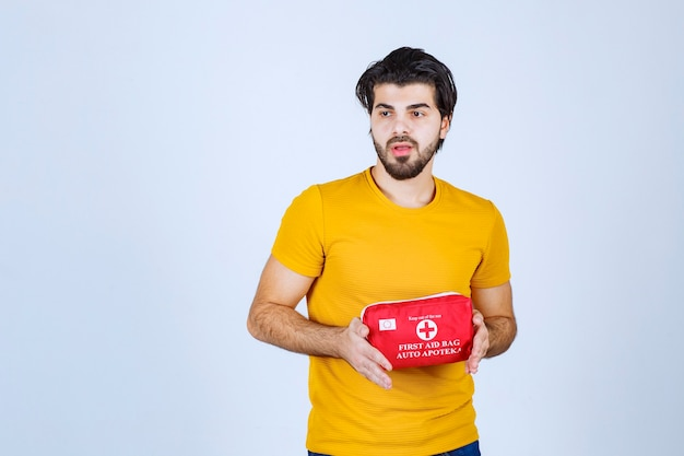 Man holding and promoting a red first aid kit.