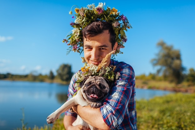 Man holding pug dog with flower wreath on head.