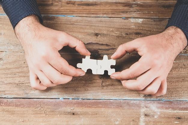 Человек, держащий кусочки головоломки на деревянной сцене