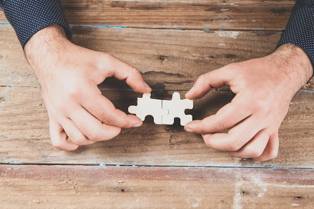 Man holding puzzle pieces on wooden scene