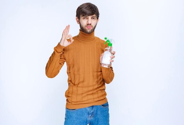Uomo che tiene in mano un prodotto chimico per la pulizia di qualità e se lo gode. Foto Gratuite