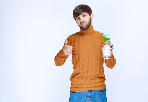 Uomo che tiene in mano un prodotto chimico per la pulizia di qualità e se lo gode.