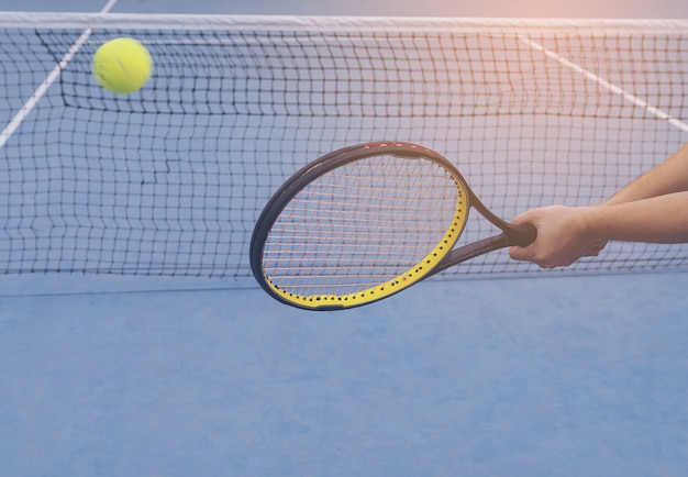 Man holding racket about to hit a ball in tennis court