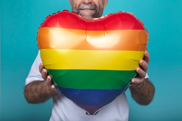 Man holding a rainbow colored balloon
