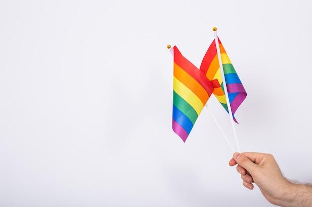 Мужчина держит в руке радужные флаги