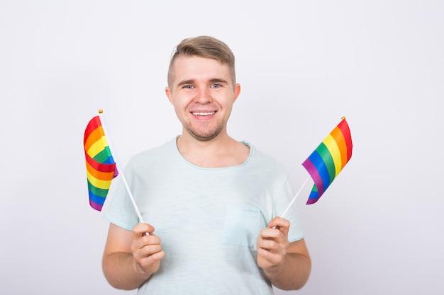 Мужчина держит в руках радужные флаги